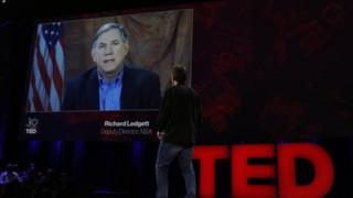 Chris Anderson on Ted stage interviewing Richard Ledgett on screen