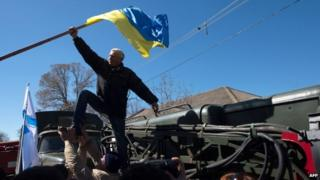 Pro-Russian protesters take down a Ukrainian flag during the storm of Novofedorivka