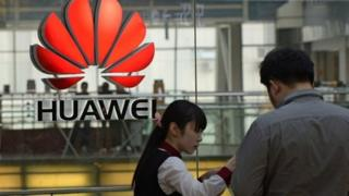 An employee (L) deals with a customer at a Huawei store in Beijing on March 24, 2014.
