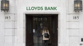 A customer walks into a branch of Lloyds Bank in London