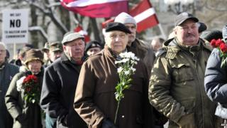 People carry Latvian flags as they march to the Freedom Monument to commemorate World War II veterans who fought in Waffen SS divisions, in Riga, Latvia, on 16 March 2014