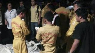 In this photo taken Monday, 24 March 2014, Thai charity workers and onlookers stand next to bodies of victims of a road accident, wrapped in white cloths, foreground, in Mae Sot, northern Thailand