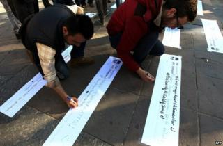 Protests write tweet-style slogans at a protest in Ankara, 21 March