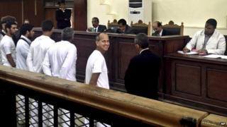 Al-Jazeera English correspondent Peter Greste, second right, smiles as he and bureau chief Mohamed Fahmy and producer Baher Mohamed stand in a courtroom along with several other defendants during their trial on terror charges, in Cairo, Egypt on 31 March 2014.