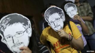 People wearing Edward Snowden masks