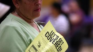 "A woman holds a flier with the words ""let's get covered"" during a healthcare signup fair in California on 28 March."