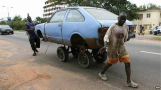 Two men push a car in a street of Accra, Ghana on 2 June 2007