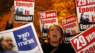 """An Israeli protesting the imprisonment of Jonathan Pollard holds up a sign reading """"enough is enough""""."""