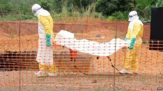 MSF workers carry the body of a person killed by the Ebola virus in Gueckedou, 1 April