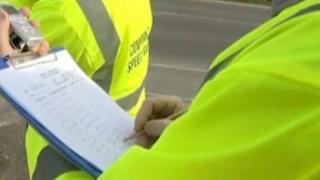 Volunteers writing registration numbers down
