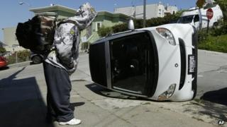 A man looks at a tipped over Smart car in San Francisco, California, on 7 April 2014
