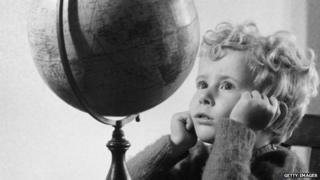A 1950 photo of a boy looking at a globe.