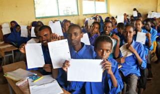 Young Somali refugees hold up the letters they've written to Syrian refugees
