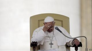 File photo: Pope Francis touches his forehead after delivering his message during the general audience in St. Peter's Square, at the Vatican, 9 April 2014