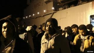 Migrants stand in line at the Sicilian harbour of Augusta April 9