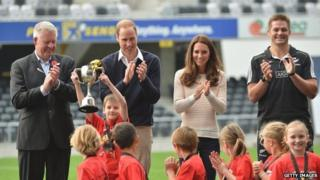 The winning tag rugby team lift the cup in front of the Duke and Duchess of Cambridge.