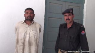 Mohammad Arif Ali (left) in police custody, 14 April 2014