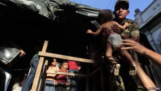 A soldier holds a child during evacuation for residents living in buildings damaged in a 1972 earthquake on 14 April 2014