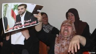 The mother of Hamza Hajj Hassan holds up a photo of the al-Manar reporter at her home in Shaath (15 April 2014)