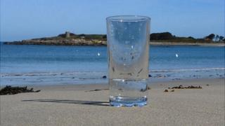 Glass of sea water at Ladies Bay, Guernsey