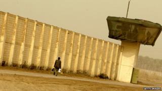 A man walks past Abu Ghraib prison (2009)