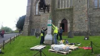 The replica stone is eased into position at Down Cathedral