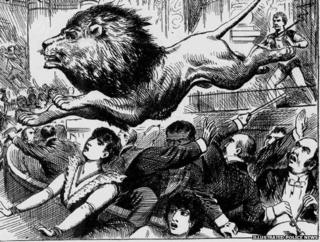 A lion leaps over members of an audience
