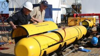Chris Minor and Curt Newport button up the Autonomous Underwater Vehicle (AUV) Bluefin-21 before it is launched off Australian Defence Vessel Ocean Shield in the search for missing Malaysia Airlines flight MH 370 on 14 April 2014