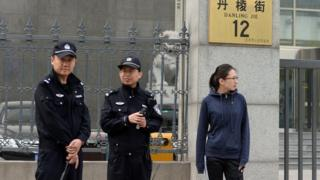 Chinese police stand guard outside a court where two Chinese anti-corruption activists Ding Jiaxi and Li Wei are on trial in Beijing's Haidian district on 8 April, 2014