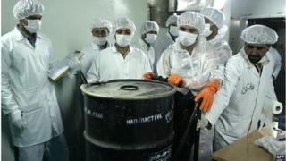 Iranian technicians remove container of radioactive uranium (file photo)
