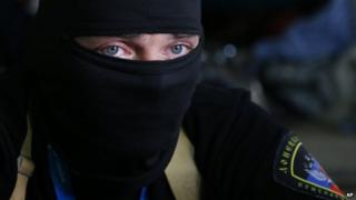 A masked pro-Russian activist guard looks through a window of the regional administration building seized in Donetsk (18 April 2014)