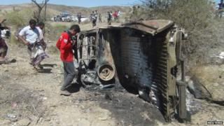 People inspect the wreckage of a car hit by an air strike in the central Yemeni province of al-Bayda, 19 April 2014