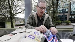 Geoff McGrath displays his Boy Scout scoutmaster uniform shirt and other scout items for the Seattle troop he led, in Bellevue, Washington 1 April 2014