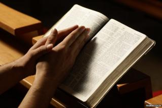 Hands in prayer over Bible