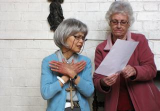 Agnes and another lady are looking at a hymn sheet and signing