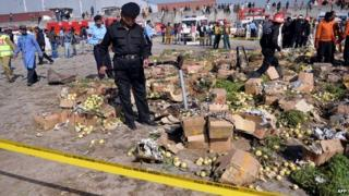 A Pakistani bomb disposal expert searches the site of an explosion at a fruit and vegetable market in Islamabad - 9 April 2014