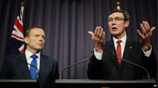 Prime Minister Tony Abbott looks on as retired Chief Air Marshall Angus Houston, the head of the Joint Agency Coordination Centre, speaks to the media during a press conference at Parliament House in Canberra, on Monday, 28 April, 2014