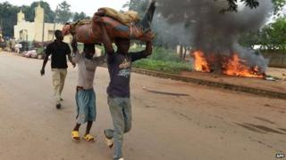 Children carry furniture as they walk past a burning car, set on fire by its owner before leaving the PK12 district, outside of Bangui, on April 27, 2014