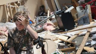 A boy takes sits in front of rubble after a tornado struck Tupelo, Mississippi, on 29 April 2014