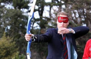 Prince William takes part in an archery lesson, whilst wearing a blindfold to simulate visual impairment, at St Dunstan's centre in 2010