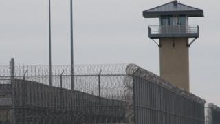 A photo of the wire fence and tower of a prison in Illinois in 2009.