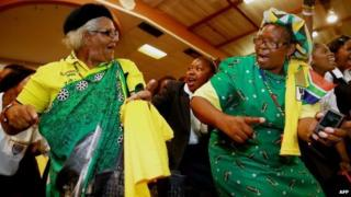 Supporters of the ruling South African political party the African National Congress (ANC) dance and sing before the arrival of the South African president during a campaign event at the Inter-fellowship Church in Wentworth township, outside of Durban, on 9 April 2014