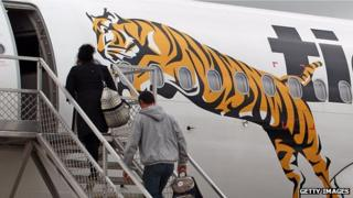 Passengers embark a Tiger Airways flight