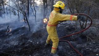 A fire fighter moves a hose while battling a fire in Logan County, Oklahoma, on 4 May 2014