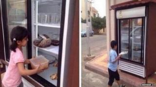Children put food in Saudi charity fridge