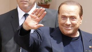 Former Italian Prime Minister Silvio Berlusconi waves as he leaves the care home