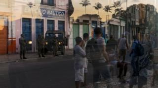 Security and passersby reflected in the glass of a shop window in Salvador, Brazil