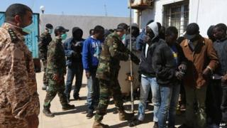 African migrants wait at a Libyan Naval forces post in Tripoli after their boat was intercepted en route to Europe and brought back to Libya, 10 April 2014