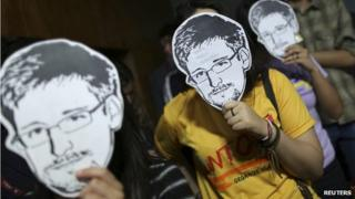 People holding Edward Snowden masks
