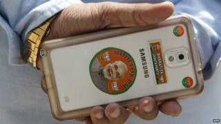 BJP worker holds a smartphone decorated with stickers bearing the image of the Chief Minister of the western Indian state of Gujarat and main opposition Bharatiya Janata Party (BJP) prime ministerial candidate Narendra Modi at the party's head office in New Delhi.